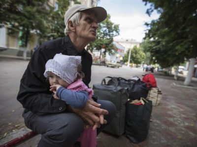 Viktor, 68, hold his 11-month-old granddaughter Alissa as they wait for a bus to leave the eastern Ukranian city of Slaviansk June 17, 2014. Residents flee Slaviansk, the pro-Russian separatist stronghold, what faced with ongoing shortages, utility outages and frequent artillery fire. Ukraine's president said on Monday he had ordered troops to regain control of the frontier with Russia to pave the way for a truce and peace talks after weeks of fighting with pro-Russian separatists. REUTERS/Shamil Zhumatov (UKRAINE - Tags: CIVIL UNREST POLITICS TPX IMAGES OF THE DAY)